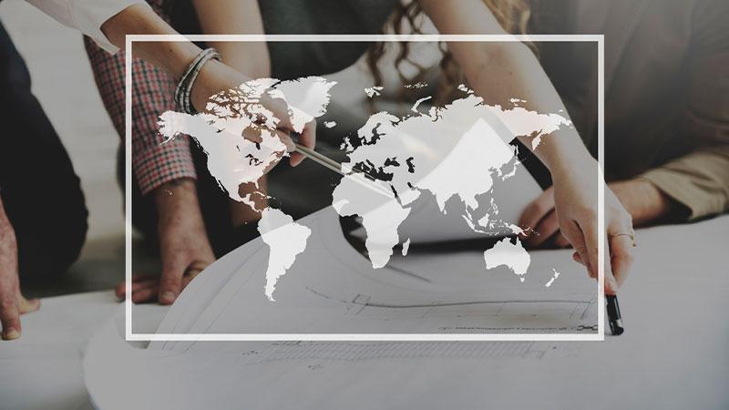 O conceito de Internacionalização vai além de vender para fora ou expandir seus negócios para outros países. Na imagem, um grupo avalia projeto ao fundo, enquanto a silhueta do mapa-mundi é apresentada no centro da imagem.